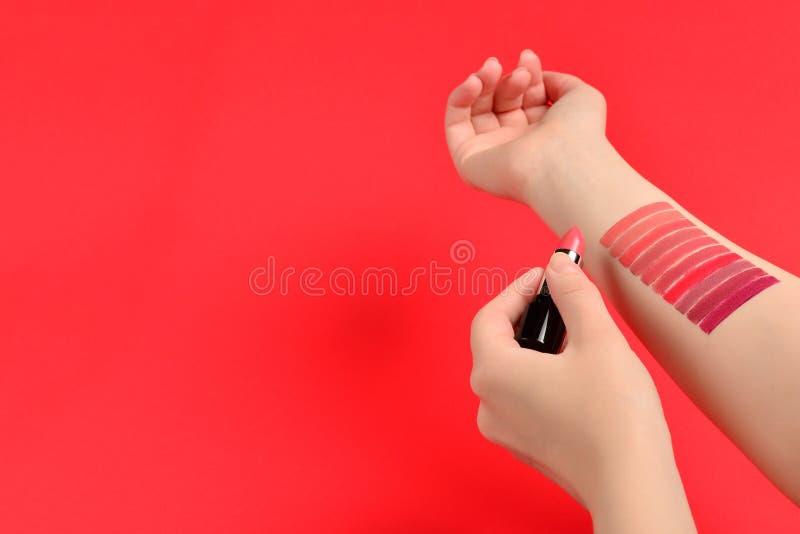 在红色背景隔绝的妇女手上的唇膏样片 免版税库存图片