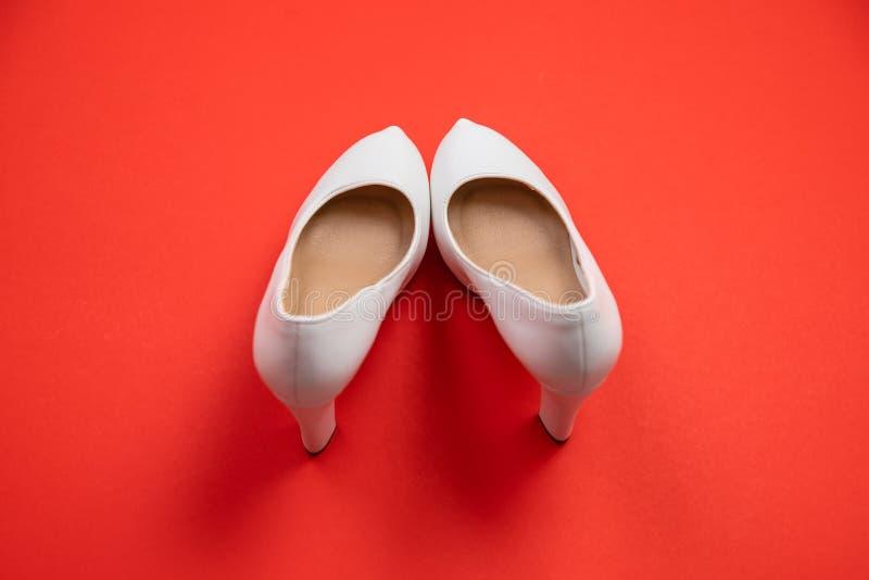 在红色背景-顶视图概念的白色高跟鞋-停顿鸽子脚趾 库存图片