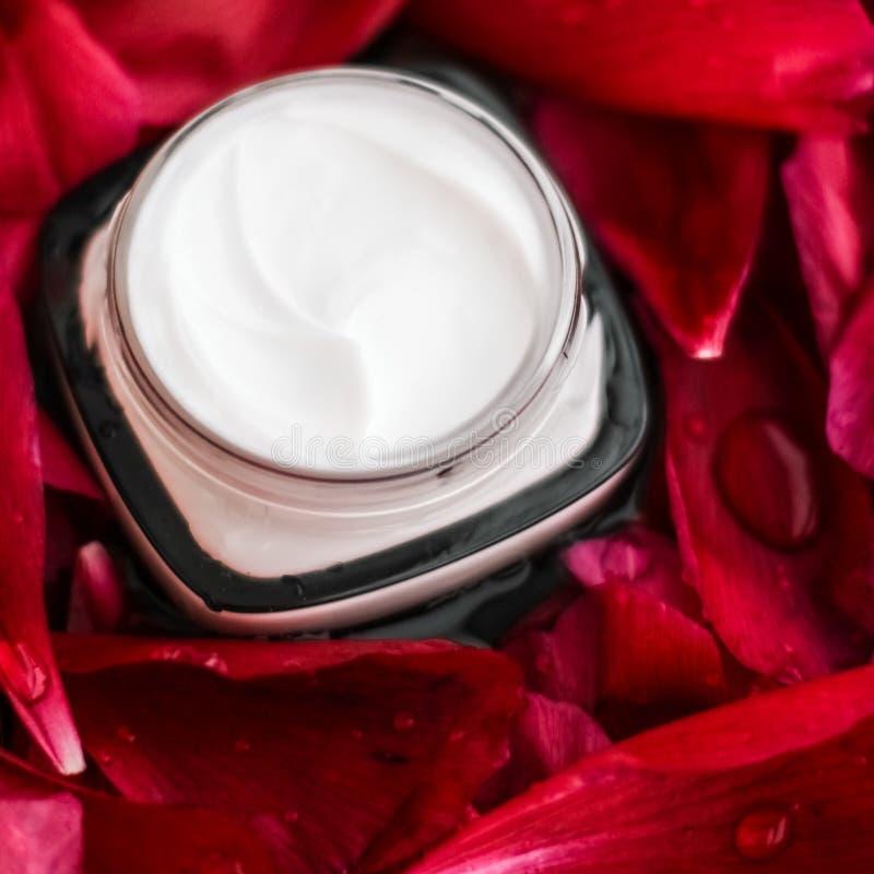 在红色花瓣和水背景,皮肤的自然科学的敏感skincare润肤霜奶油 免版税库存照片