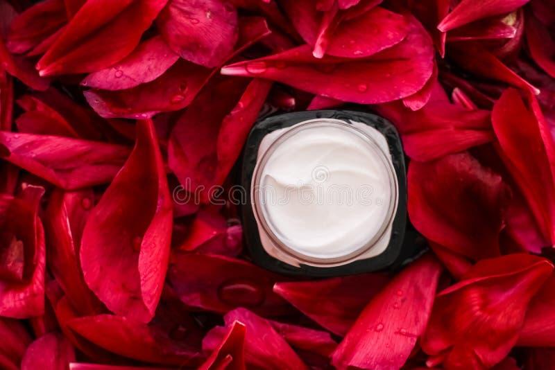 在红色花瓣和水背景,皮肤的自然科学的敏感skincare润肤霜奶油 免版税库存图片