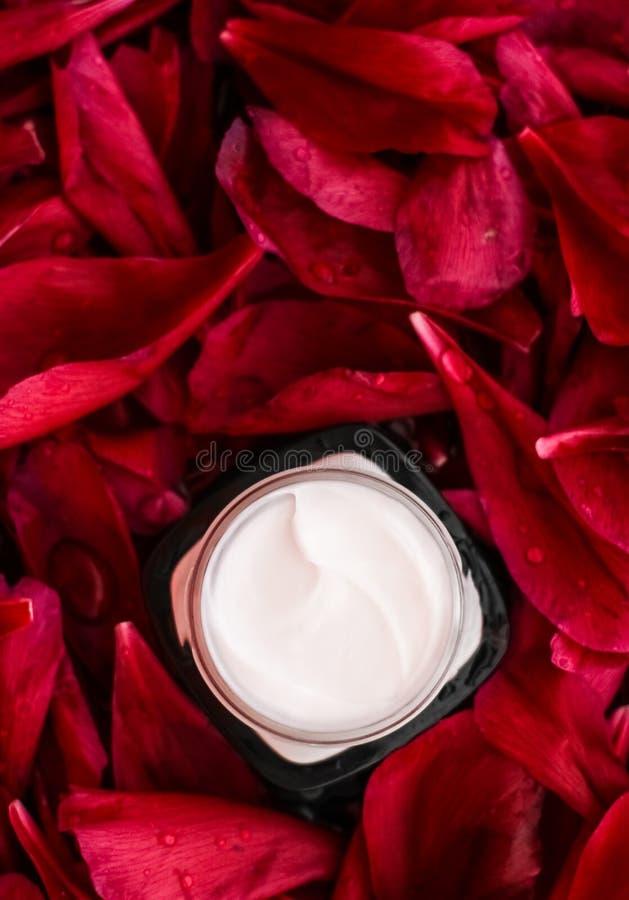 在红色花瓣和水背景,皮肤的自然科学的敏感skincare润肤霜奶油 库存照片