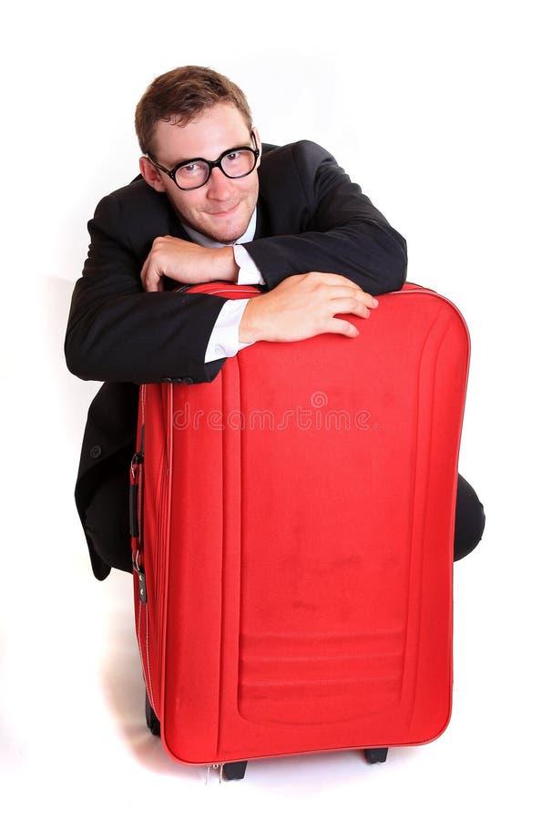 在红色行李后的年轻商人 免版税库存照片