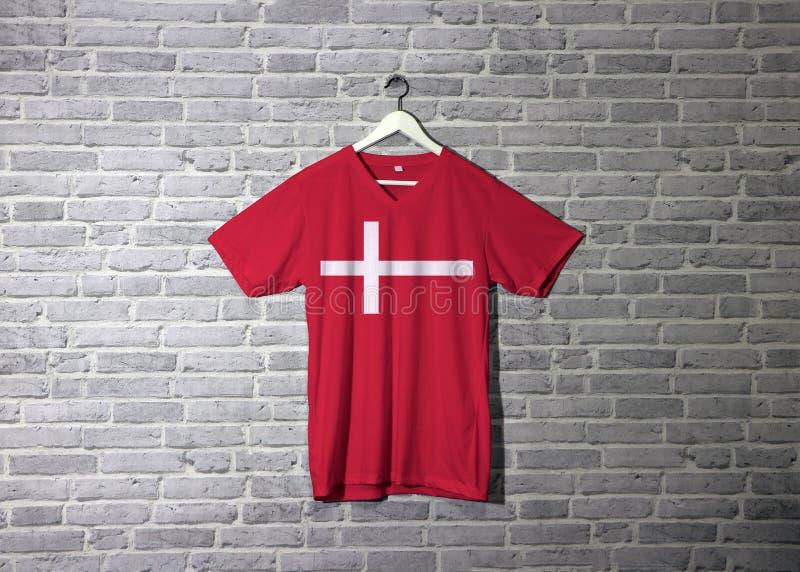 在红色衬衣的丹麦旗子和垂悬在有砖样式墙纸的墙壁上 库存图片