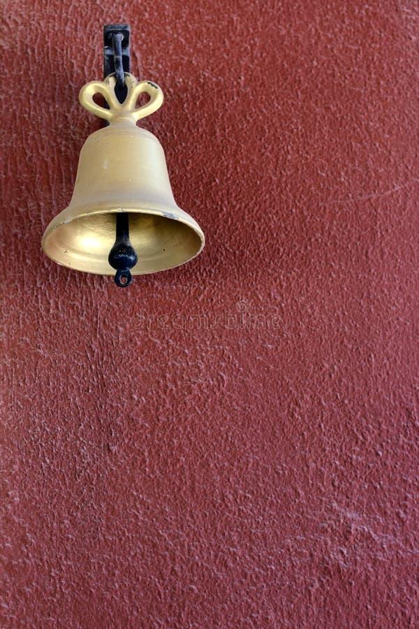 在红色被绘的墙壁上的金响铃 库存图片