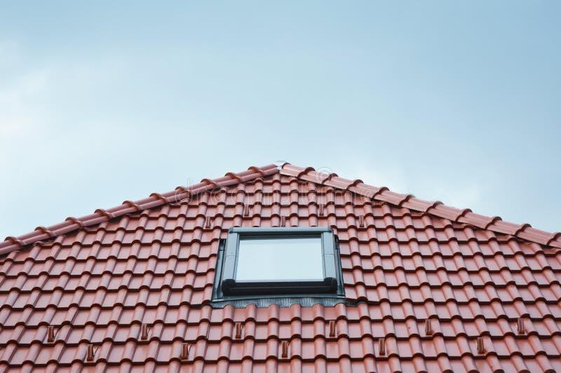 在红色议院黏土陶瓷砖屋顶的现代屋顶天窗窗口 屋顶建筑 库存照片