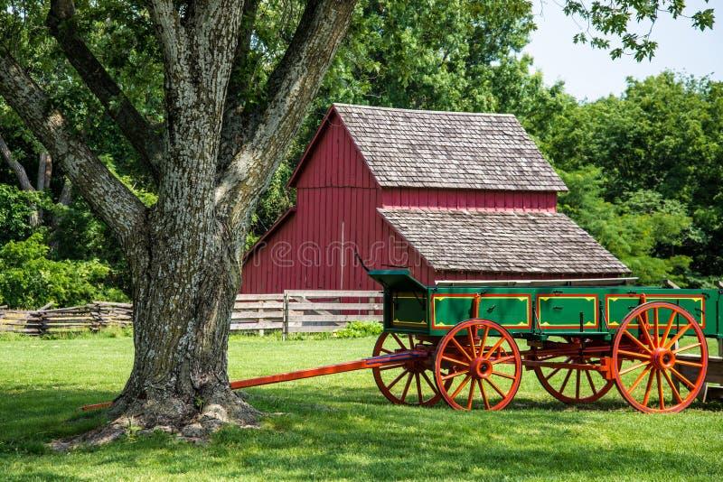 在红色谷仓前面的红色和绿色老古色古香的无盖货车 免版税库存图片