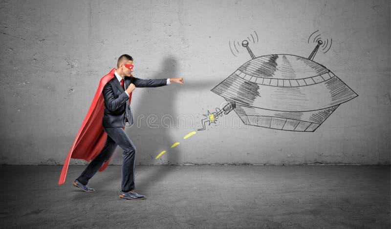 在红色超级英雄海角投掷的拳打的一个商人在碰撞在他的飞碟的壁画 免版税图库摄影