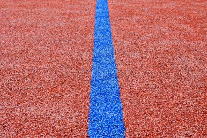 在红色运动场的蓝线 复制空间 体育纹理和背景 库存照片