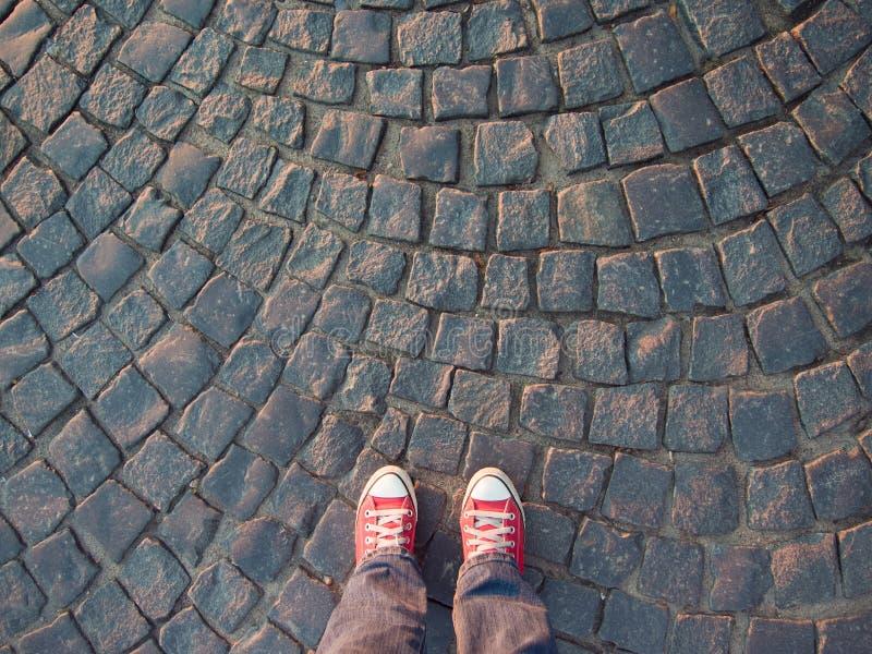 在红色运动鞋的脚在路面顶视图,不拘形式的样式 库存图片
