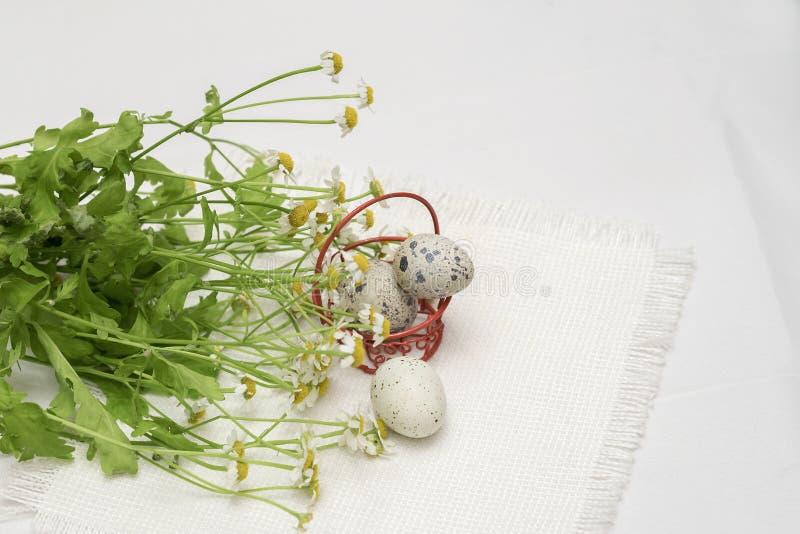 在红色金属篮子和鲜花,轻的土气餐巾,顶视图的鹌鹑蛋 复活节的,春天概念,有机 库存图片