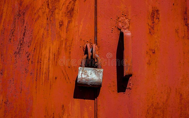 在红色金属门的生锈的老挂锁以破裂和抓痕 水平的难看的东西纹理 免版税图库摄影