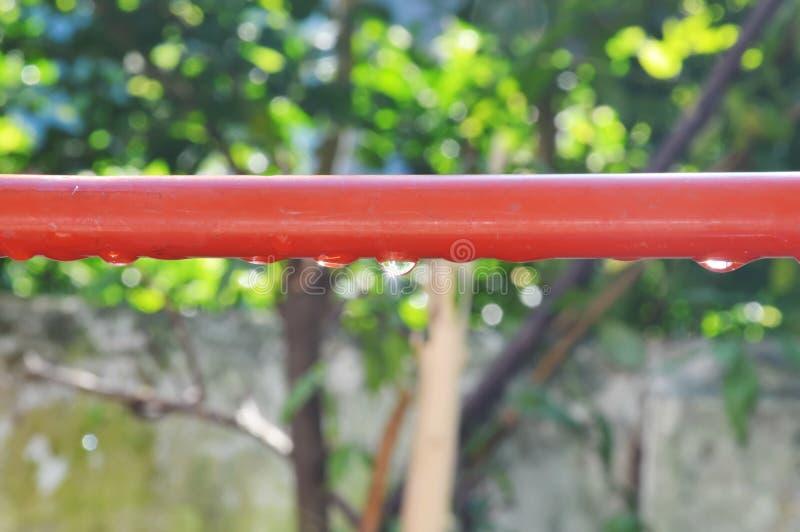 水滴在红色铝晾衣绳反射阳光的 库存图片