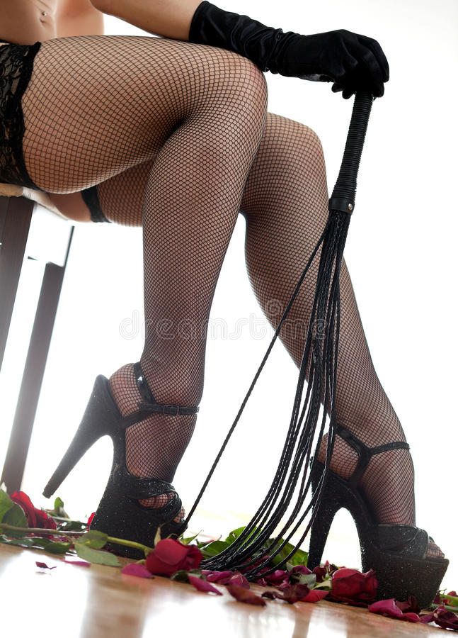 女性腿和鞭子 免版税库存图片