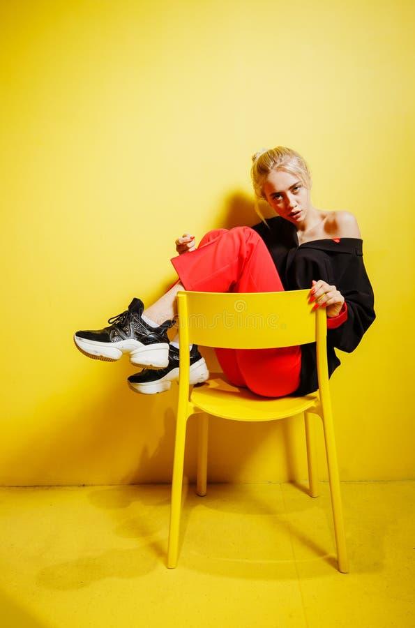 在红色长裤和黑jacke possing的打扮的年轻时尚女孩博客作者坐凳子在有黄色的屋子里 免版税图库摄影