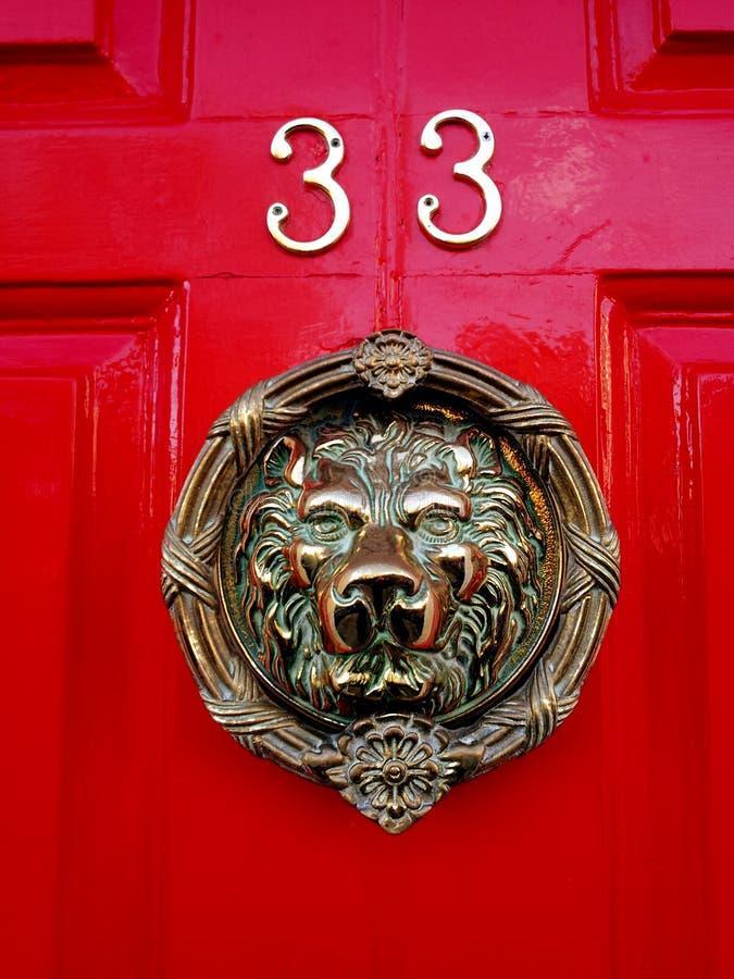在红色门与动物面孔的第33的敲门人 库存照片