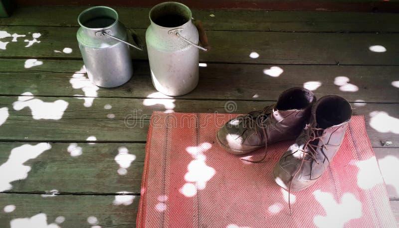 在红色门前的擦鞋棕垫和两个葡萄酒铝牛奶罐头的老棕色起动在木地板上 库存照片