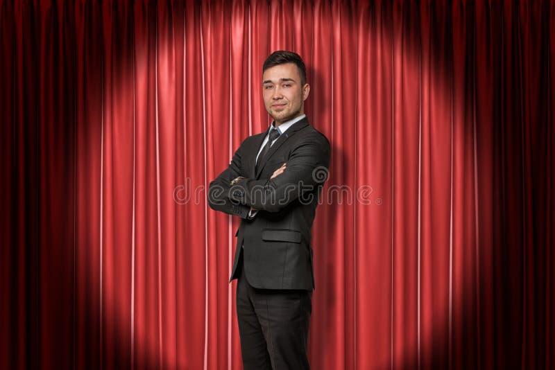 在红色阶段帷幕背景的年轻微笑的商人 图库摄影