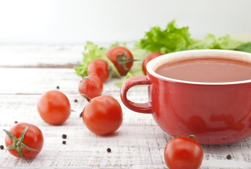 在红色陶瓷碗的蕃茄汤在土气木背景 Hea 免版税库存图片