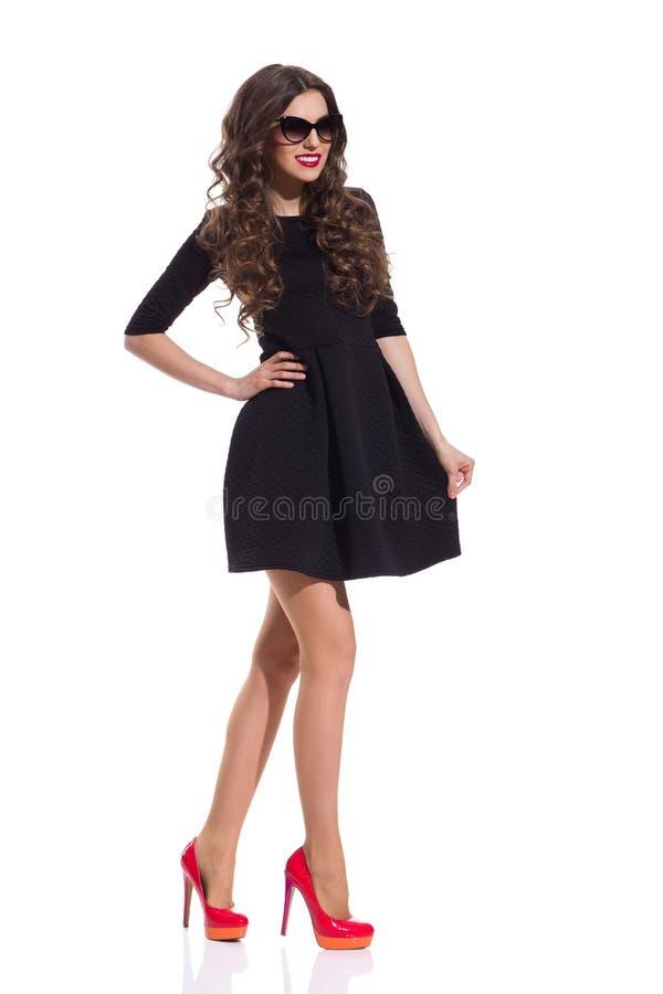 在红色高跟鞋和黑套衫连超短裙的时装模特儿 图库摄影