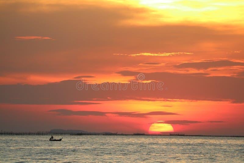 在红色黄色天空后面平衡的云彩的日落在天际海 免版税库存图片