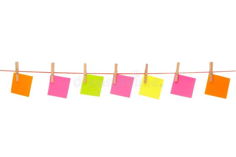 在红色绳索垂悬的五颜六色的stickies被隔绝 免版税库存图片