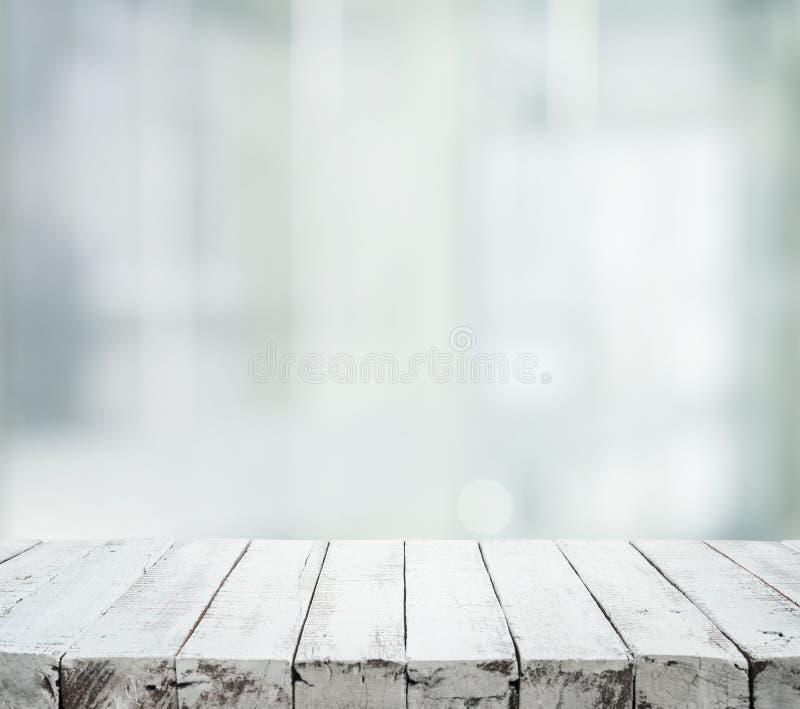 在红色bokeh背景的美丽的白色木纹理桌 免版税库存照片