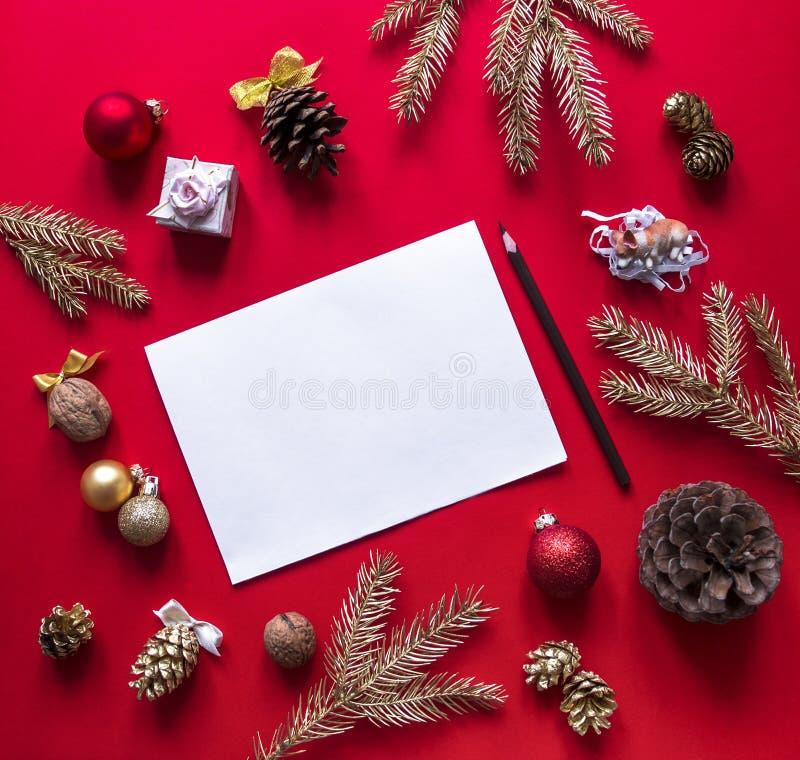 在红草莓背景圣诞节装饰和云杉的金子分支在圈子,白色板料铅笔被安排 图库摄影