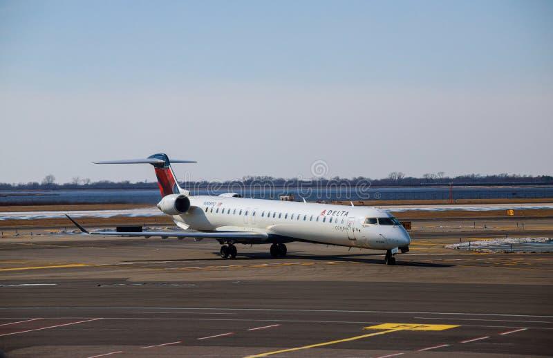 在约翰F的三角洲飞机 肯尼迪国际机场在一个跑道机场的飞行离开在美国 免版税图库摄影