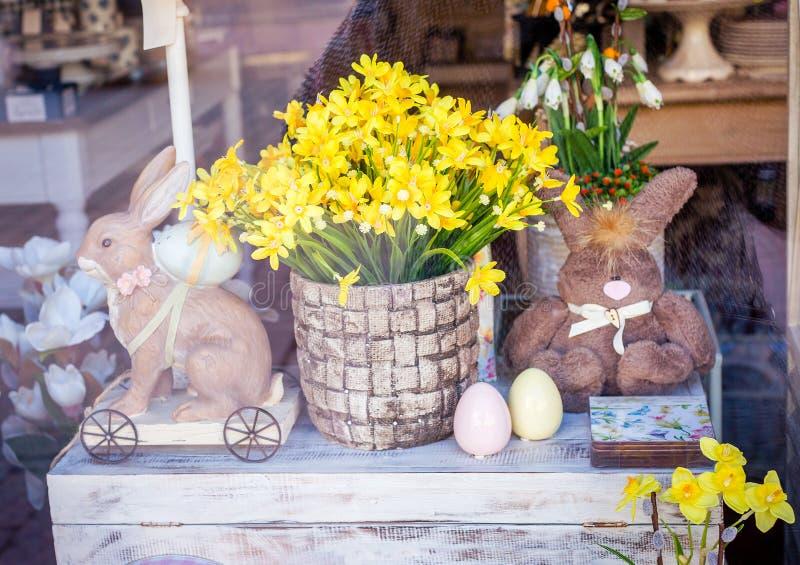 在纪念品店的陈列室的复活节题材 花、玩具和复活节彩蛋在胸口 免版税图库摄影