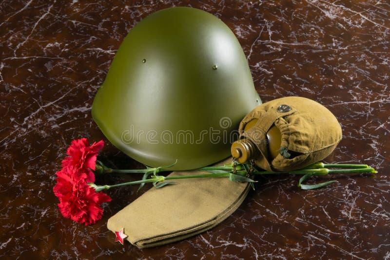 在纪念碑、两支红色康乃馨、旅行水壶、军事盔甲和盖帽的背景 免版税库存图片