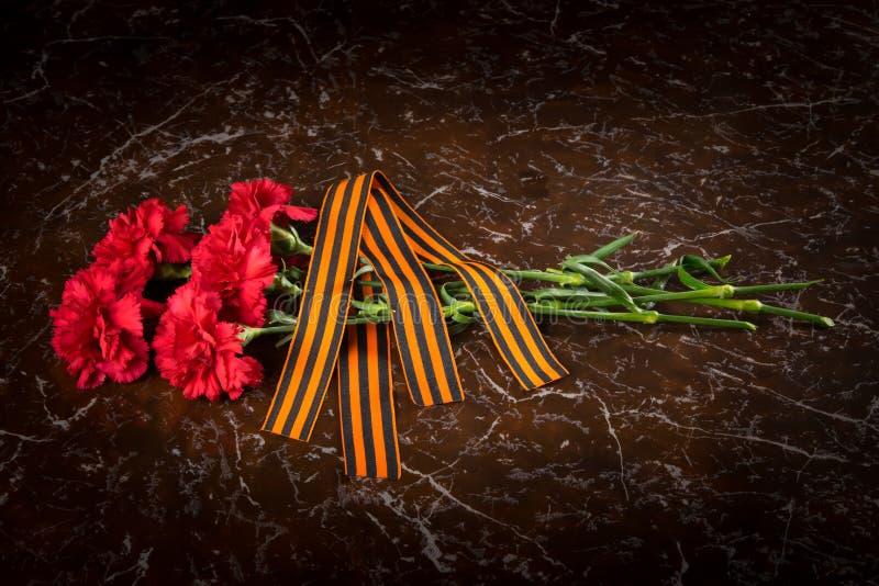 在纪念碑的大理石平板,是康乃馨和圣乔治丝带花束  库存照片