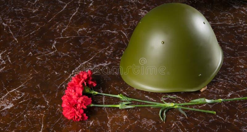 在纪念碑的大理石平板,有两支康乃馨和一样军事头饰,盔甲 库存图片