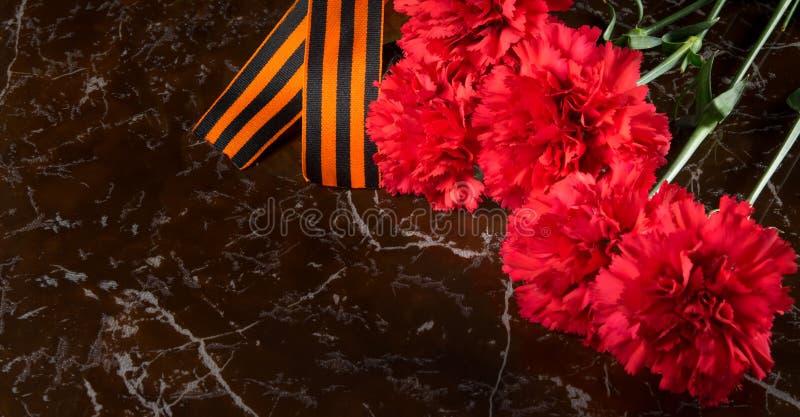 在纪念碑的大理石平板,有康乃馨花束,圣乔治的丝带,并且在左边有一个地方为 库存照片