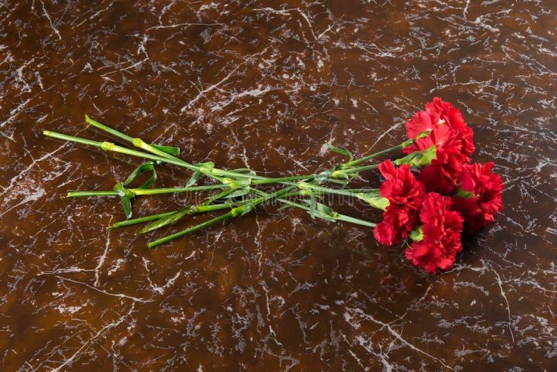在纪念碑的大理石平板,有红色康乃馨花束,有题字的一个地方 库存图片