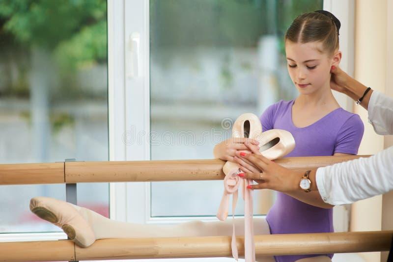 在纬向条花附近的小的芭蕾舞女演员训练舒展 免版税库存图片