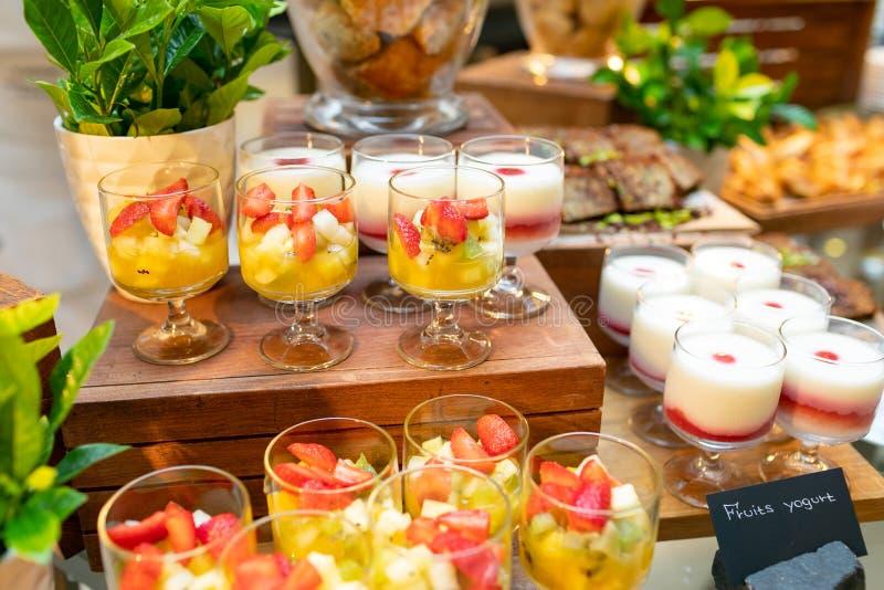 在纯净玻璃花瓶、水果沙拉和水果酸牛奶的各种各样的曲奇饼在玻璃杯子 免版税库存照片