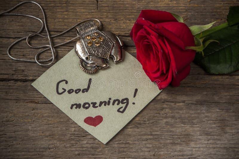在纸、红色玫瑰花和装饰el的早晨好文本 免版税图库摄影