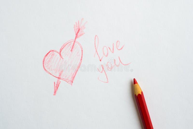 在纸、题字爱您和在白皮书的一支红色铅笔画的心脏 免版税库存图片