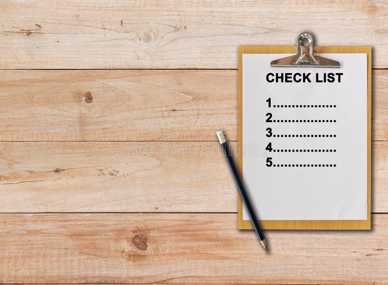 在纸剪贴板的清单在木背景 免版税库存照片
