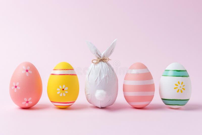在纸包裹的复活节彩蛋以一个兔宝宝的形式用五颜六色的复活节彩蛋 最小的复活节概念 免版税库存照片