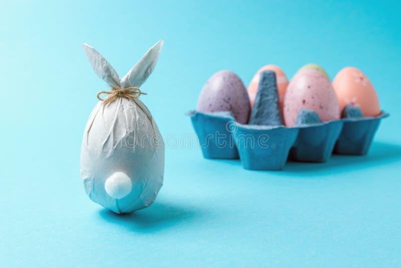 在纸包裹的复活节彩蛋以一个兔宝宝的形式用五颜六色的复活节彩蛋 最小的复活节概念 免版税库存图片