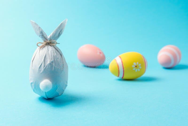 在纸包裹的复活节彩蛋以一个兔宝宝的形式用五颜六色的复活节彩蛋 最小的复活节概念 免版税图库摄影