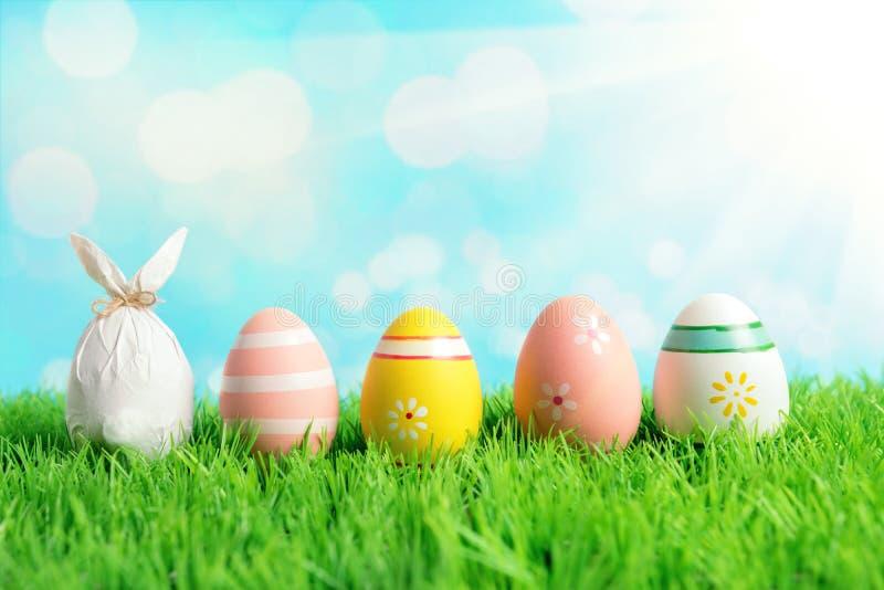 在纸包裹的复活节彩蛋以一个兔宝宝的形式用在绿草的五颜六色的复活节彩蛋 春天假日概念 库存图片