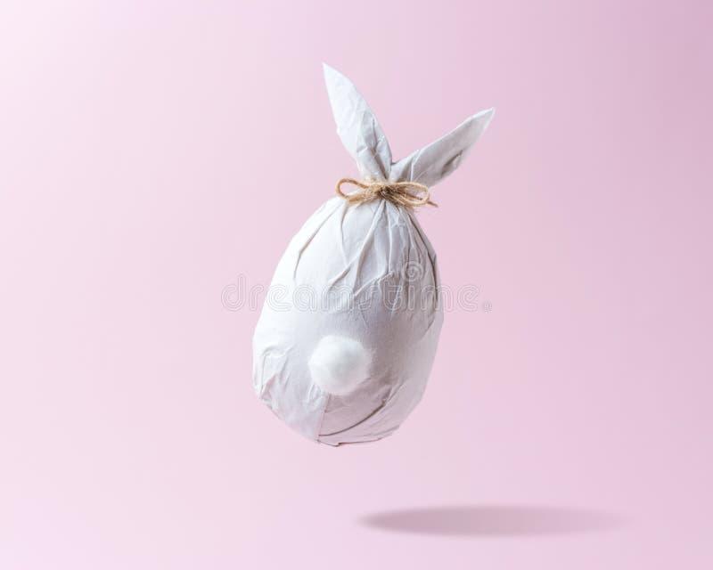 在纸包裹的复活节彩蛋以兔宝宝的形式 最小的复活节概念 库存图片