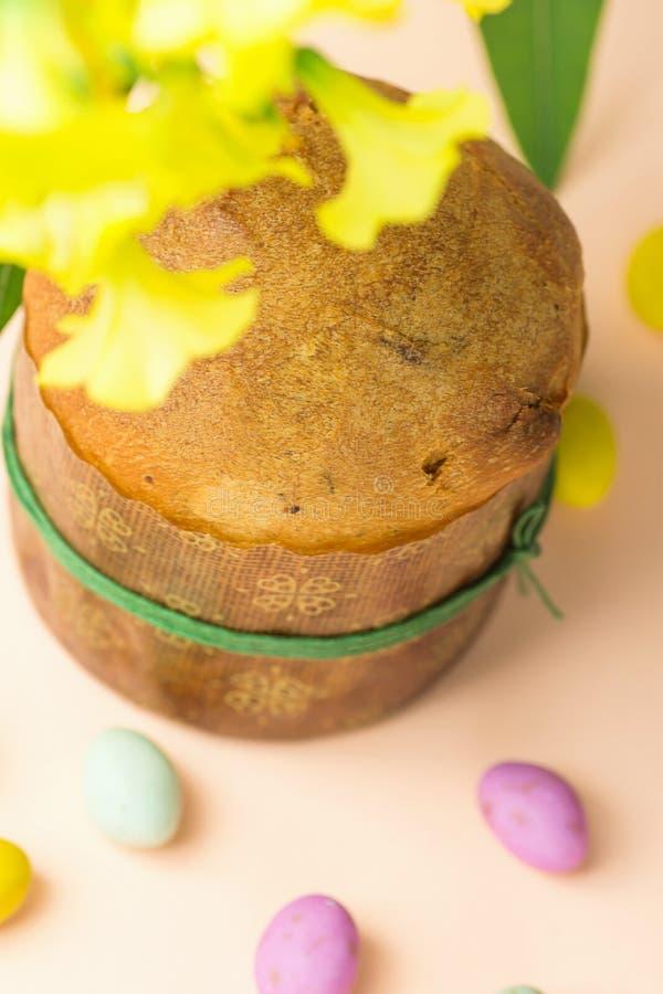 在纸在桃红色桌面花驱散的形式多彩多姿的有斑点的巧克力糖鸡蛋的自创复活节甜蛋糕意大利节日糕点 免版税库存图片