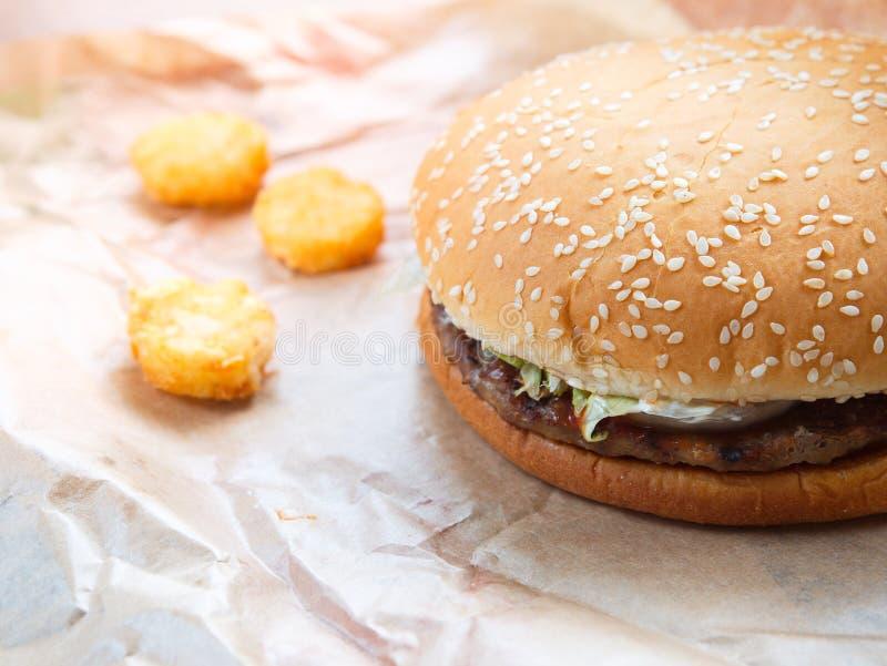 在纸持有人的汉堡包牛肉和马铃薯煎饼在餐馆,汉堡包用牛肉和菜 库存图片