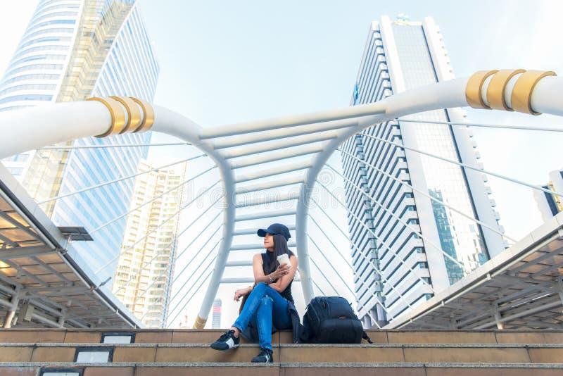 在纸杯的旅客妇女坐的和饮用的咖啡在城市镇、都市背景,街道样式,愉快的楼梯和享用 库存照片