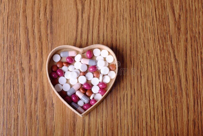 在纸板心脏形状的药片 库存照片