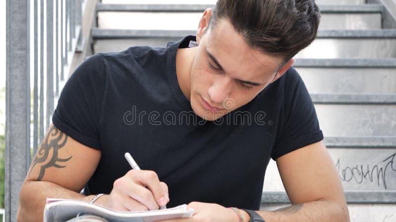 在纸板料的年轻人文字与笔 免版税库存图片