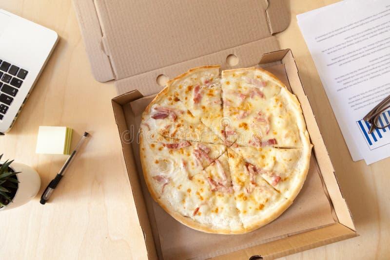 在纸板箱的意大利薄饼在工作书桌,顶视图上 免版税库存照片